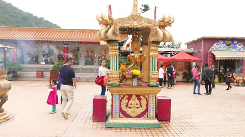 Buddha sculpture sitting in small pavilion at monastery courtyard Footage