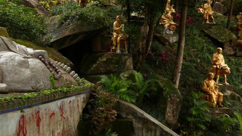 Golden Buddhas sculptures on grassy hillside, Ten Thousand Buddhas monastery Live Action