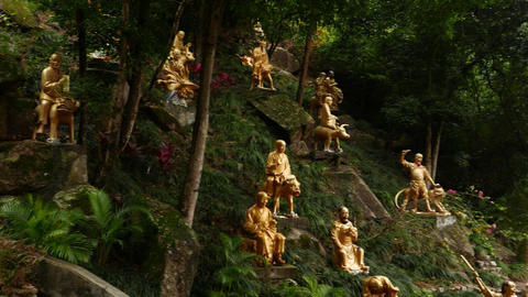 Stony lying Buddha sculpture in foresty hillside, golden statues on slope Footage
