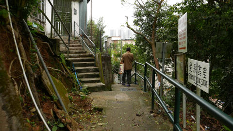 Pathway in village on the hill, concrete stairs, handrails, man walk and stand Footage