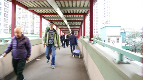 Ordinary people walking at footbridge, camera move through pedestrian passage Footage