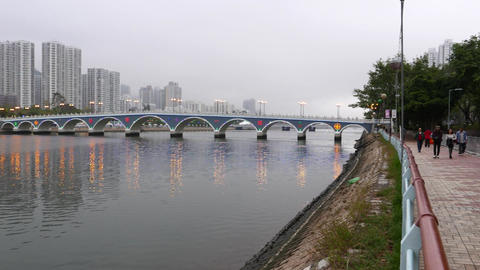 River in city, evening, bridge and promenade, people jogging walking Footage