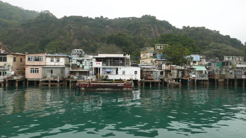 Village panning shot, huts on piles over vivid turquoise bay waters Footage