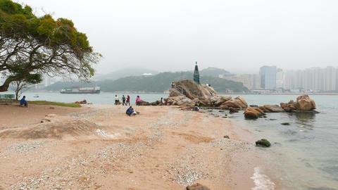 Scenic beach, rocks, stones, lighthouse, tree and foggy Hong Kong island Footage