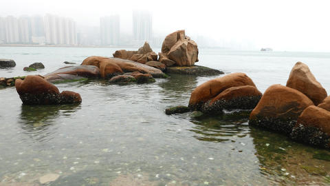 Beach stones in rain, camera move closer, raindrops and foggy horizon Footage