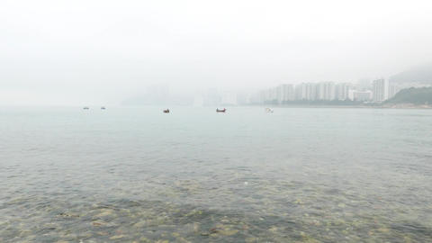 Stones on beach, fisherman boats on water, waves wash downwards Footage