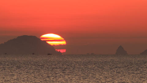 large disk of sun appears from behind hill sea at foreground Footage