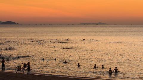vietnamese people swim in sea bike on sand beach at sunrise Footage