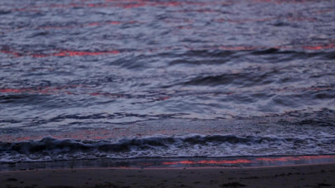 Sea waves gently wash up after red sunset. Slow motion. Nobody Footage