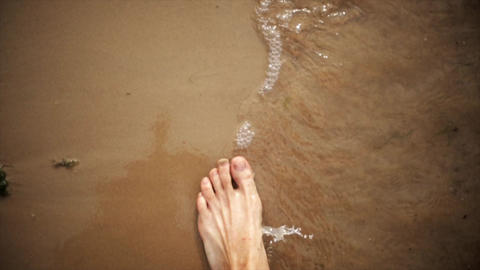 Man walk on sand beach, waves gentle wash his feet. Summer. First person view Live Action