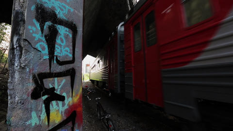 Moving suburban electric train uner bridge. Summer day. Bicycle left. Graffiti Footage