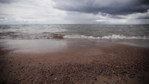 Small sea waves on beach with tiny stones. Grey cloud sky. Summer. Slider pan Footage