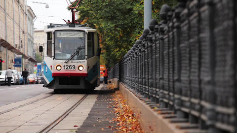 Tram drive on rails along fence. Autumn day. City. Janitor at work Footage