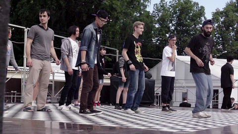 People on stage. Man show dance movements, people repeat. Slow motion. Festival Footage