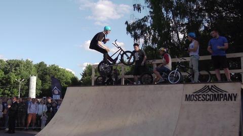 Boy make extreme jump on BMX bicycle skate park overturn steering wheel in air Footage
