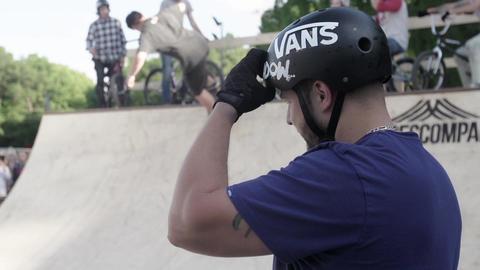Man in helmet watch at skater in skate park. Summer day Footage