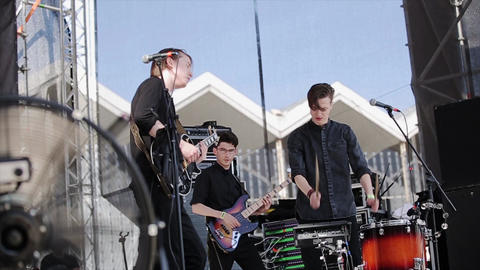 Rock music band perform on stage at live festival. Guitarists, drummer Footage