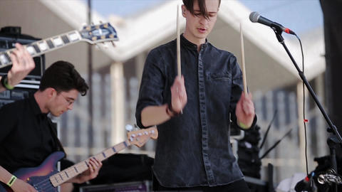 Rock band perform on stage at live festival. Soloist knocks drumsticks on drums Footage