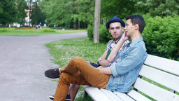 Busy friend. Boy try talk with friend sit on bench, but he start talk on phone Live Action