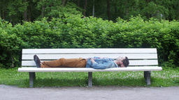 Young boy lie on white bench in green summer park. stand up and go. Rest, relax Footage