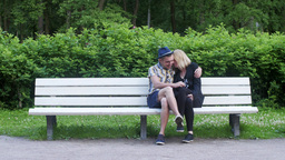 In love couple come and sit down on bench in green summer park. Embrace Footage
