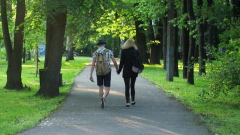 Back side of young walking in love couple with backpacks. Summer. Holding hands Footage
