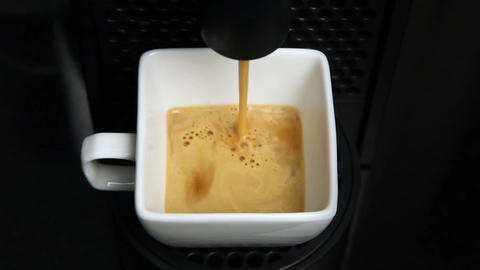 Coffee maker pouring coffee into a cup, close up Footage