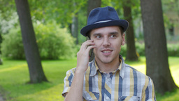 Portrait of boy in hat talking on phone, smile. Outdoor. Summer park. Gladness Live Action