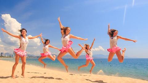 cheerleaders dance squat show poses on beach against sea Footage