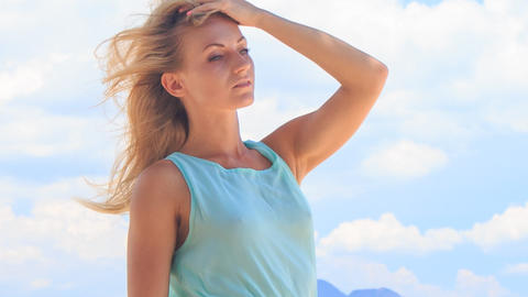portrait of blonde girl smoothing hair under wind Footage