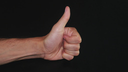 Thumbs up. Close up hand on black background. Like Footage