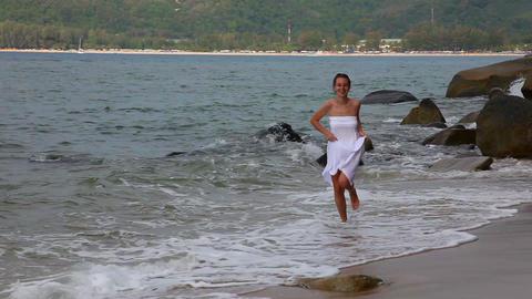 Girl runs along the beach Footage