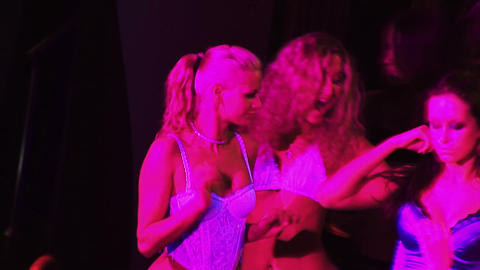 Female dancing show on a scene in club in night dresses, bathing suits, underwea Live Action