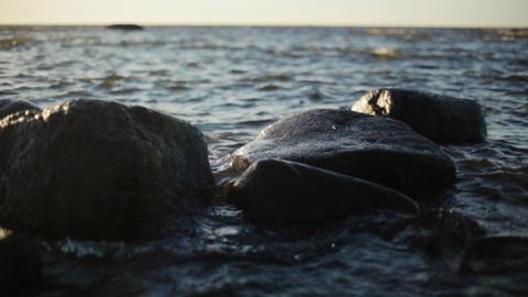 Small waves crash on the rocks on sea coast under sunshine. Nobody. Slow motion Live Action