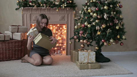 Young woman with gifts in front of Christmas tree Footage