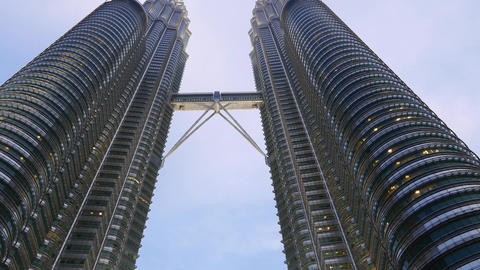 Smooth pan dolly shot Petronas Twin Towers Skybridge in dusk, up view vertical Footage