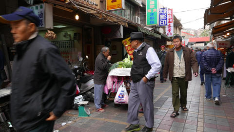 Aged hawker sell greengrocery on market street, quick look while walk aside Footage