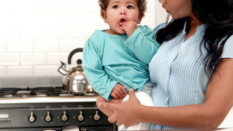 Smiling mother carrying baby boy in kitchen Footage