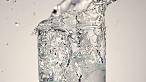 Ice cubes falling into glass of water Footage