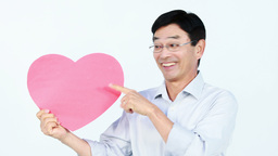 Smiling Asian man holding a pink heart Footage