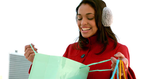 Pretty smiling girl looking in a shopping bag Footage