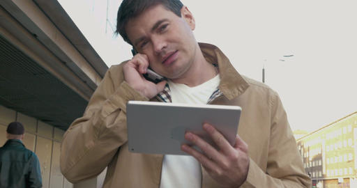 Busy Man with Smartphone and Tablet Outdoor Live Action