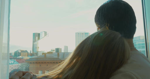 Young couple enjoying city view through the window Footage