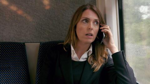 Businesswoman using phone on the train ビデオ
