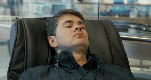 Man having a rest in massage chair Live Action