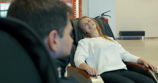 Young woman enjoying massage in special arm-chair Footage