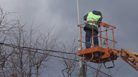 Ungraded: Worker In Cradle Of Skylift Colors Lamppost With White Paint stock footage