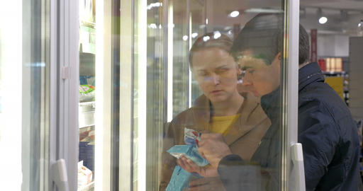 Young family couple taking products in fridge section Footage