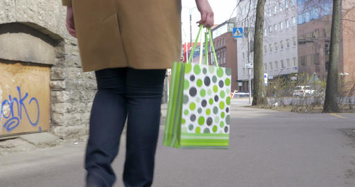 Girl with shopping bag walking in the street Footage