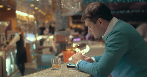 Man using cell and having alcohol drink in the bar Footage